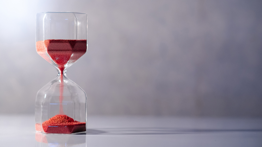 Red sand running in hourglass